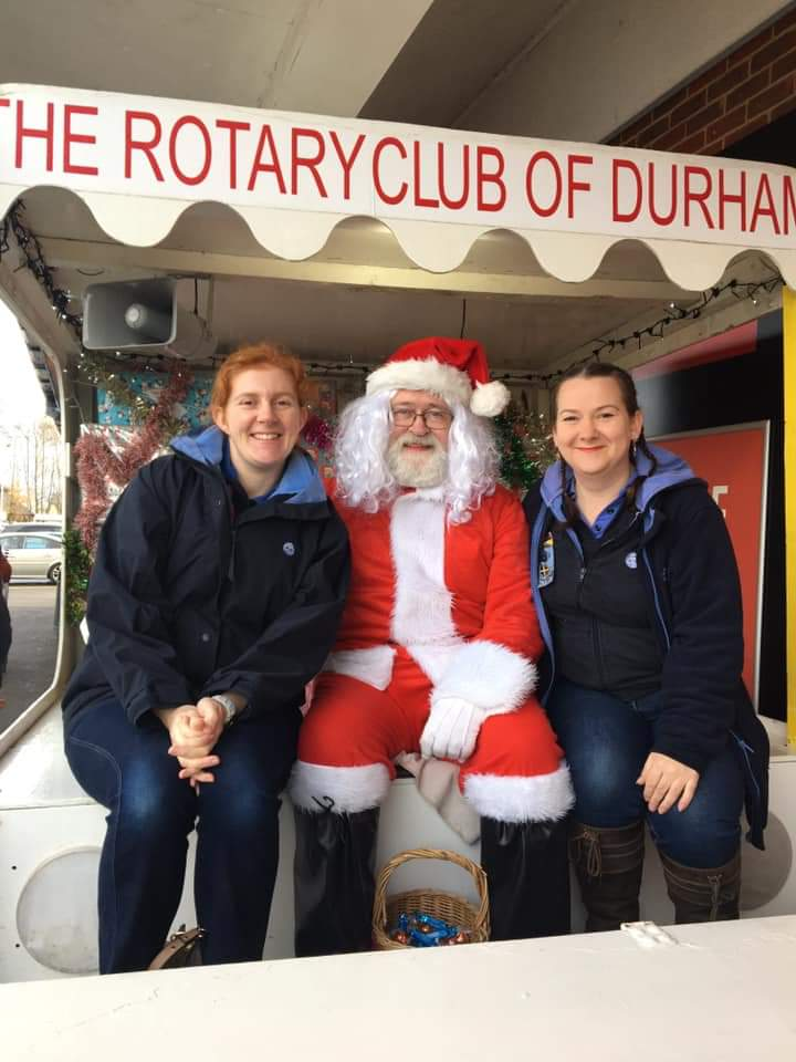 2 Leaders pose next to Santa on the Rotary Club of Durham branded sleigh.